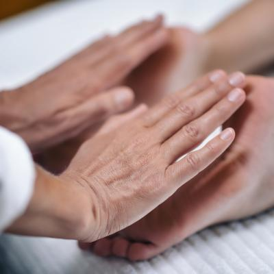 Image: Reiki practitioner applying healing to patient's feed.