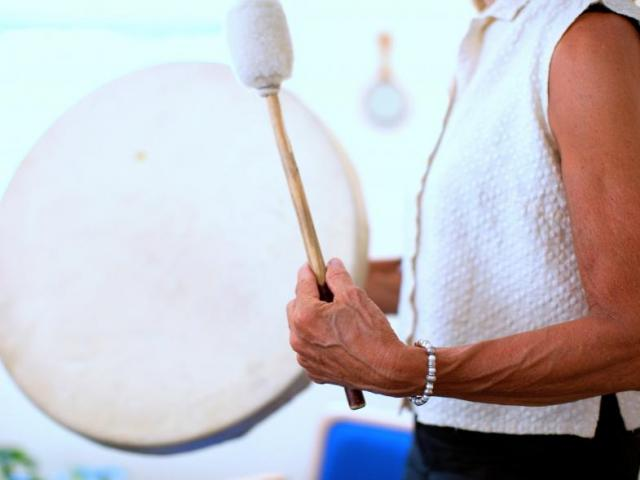 Image: woman with drum and mallet.
